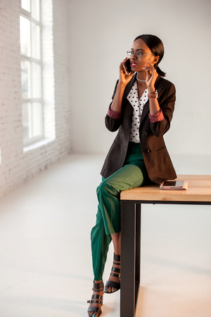 African american young businesswoman sitting on the table and talking on hte phone in her office. Standard-Bild
