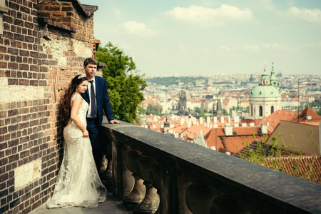 stylishly: Stylishly dressed newlywed couple is standing on the old meadieval balcony and enjoying the panorama of Prague.