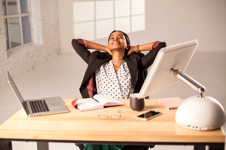 african american woman: Happy businesswoman sitting at her working place and relaxing. Stock Photo