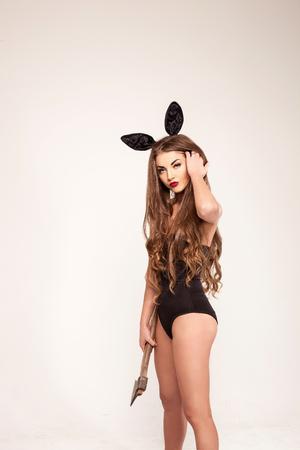 Mooi meisje met zeer lang haar dat een bijl houdt en combinatie en konijn-oren draagt