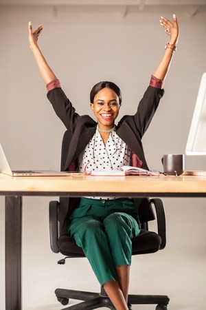 african american woman: Vertical shot of happy businesswoman with her hands up. Woman sitting in the office.