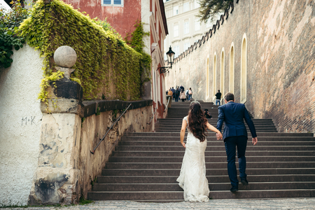 The horizontal back view of the beautiful newlyweds going up the ancient stairs of Prague