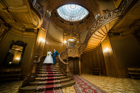 bajando escaleras: Horizontal view of the happy newlyweds holding hands while going down the stairs of the ancient building.
