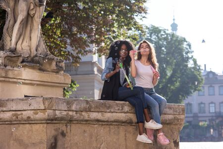 afroamerican: Young and attractive women sitting near the monument in the center of the city and blowing bubbles. Girls wearing jeans and snickers. Casual lifestyle concept.