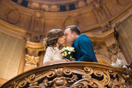 Kissing newlyweds while standing on the old baroque balcony with the wedding bouquet.