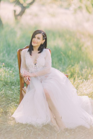 The smiling woman in the long white dress and hair accessories is sitting on the old moders chair in the field.