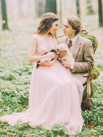 luxury room: The lovely vertical photo of the bride with long curly hair holding the brown ferret and sitting on the groom`s laps while the grooms is holding the white ferret. The wood composition.