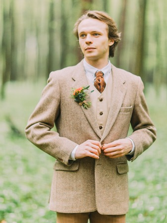 flashlights: The portrait of the handsome blond man in the vintage suit is buttoning hir jacket decorated with mini-bouquet. Stock Photo