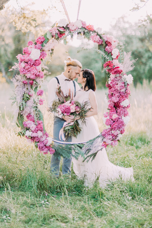 The close-up portrait of the newlyweds holding the bouquet and standing behind the wedding peonies arch in the sunny forest.