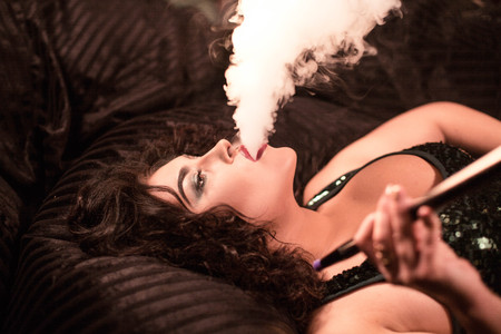 Sexy young woman with hookah pipe in her hand. Woman exhaling a cloud of hookah smoke.