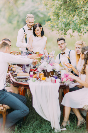 The lovely portrait of the newlyweds cutting their wedding cake and their guests. The table setting of the wedding dinner located in the sunny field.