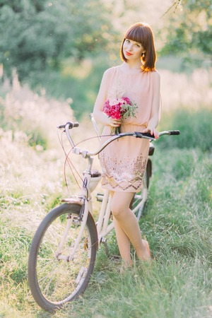 The bridesmaid with short haircut in the pink dress with glitters holding the small pink bouquet near the bicycle in the sunny field.
