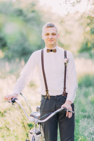 Smiling best man in the dark suit and black suspenders decorated with flowers is holding the bicycle in the middle of the green sunny field. Stock Photo