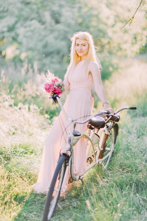 The vertical photo of the bridesmaid in the long light pink dress holding the pink bouquet and sitting on the bicycle in the sunny forest.