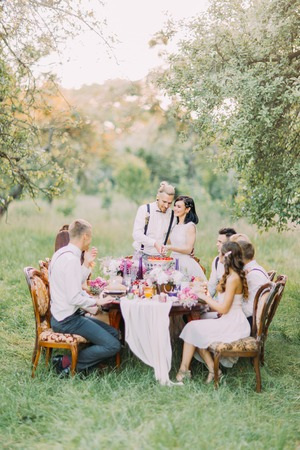 Lovely newlyweds are cutting their fisrt piece of the wedding cake together in the forest. The gueats are sitting at the table and observing it.