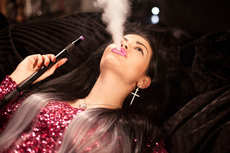 Pretty woman with nice makeup and hairstyle exhaling hookah smoke. Stock Photo