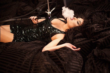 Pretty curly woman exhaling a cloud of hookah smoke. Woman in short deep neckline dress. Stock Photo