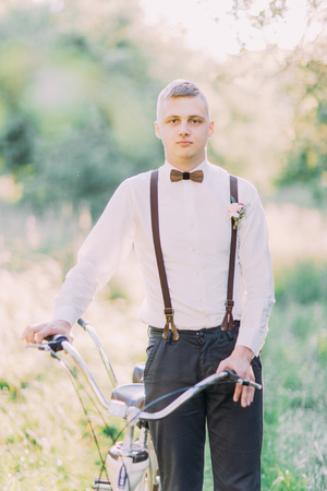 The close-up portrait of the best man in dark pans, white shirt, wooden butterfly and black suspenders with flowers, holding the bicycle at the background of the forest. Stock Photo
