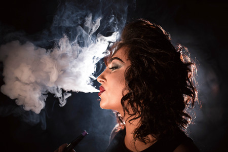 Portrait of woman with her eyes closed and exhaling hookah smoke.