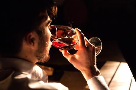 Close-up die van de mens is ontsproten die rode wijn proeft.