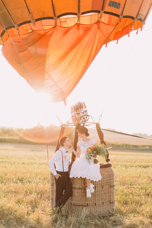 The vintage dressed bride with the bouquet is petting the face of the smiling groom while sitting on the airbaloon basket in the sunny field.