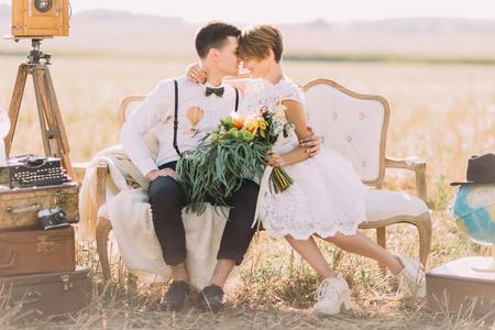 Die schöne Nahaufnahme horizontale Porträt der Jungvermählten sitzen Kopf-an-Kopf auf dem Sofa. Die Braut hält die bunte Hochzeit Bouquet im Hintergrund des Feldes.