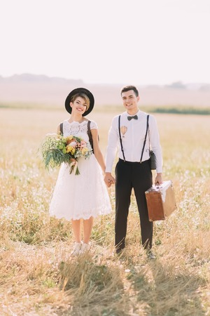 The front full-length portrait of the vintage dressed newlywed couple holding hands and smiling at the camera at the background of the sunny field. Stock Photo