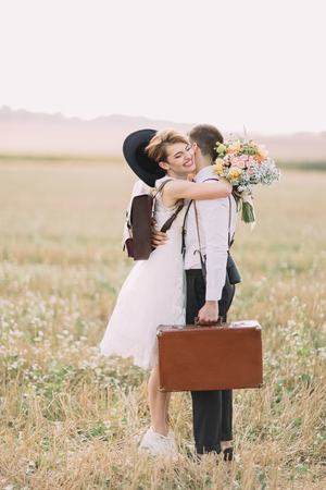 The lovely side portrait of the happy vintage dress newlyweds hugging in the sunny field.