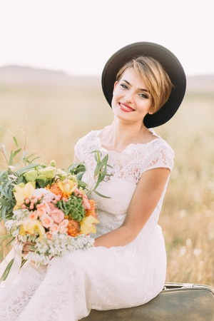 The close-up vertical portrait of the blonde bride in the vintage dress and hat holding the big colourful bouquet, sitting on the old-fashioned suitcase and smiling at the camera.