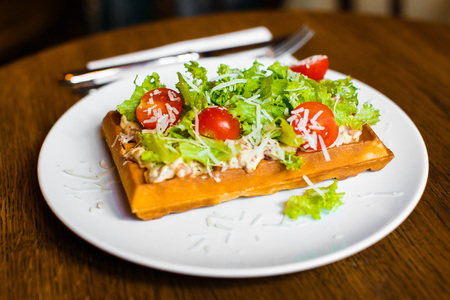 The side photo of the vegetable belgian waffles with tomatoes, salat and cheese Stock Photo