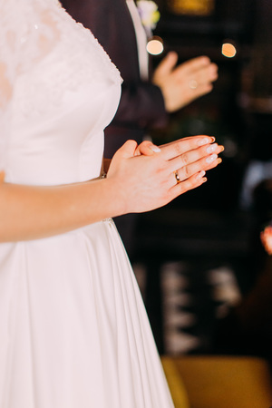 The close-up view of the hands of the praying bride