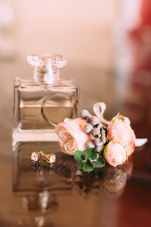 The composition of the parfum, golden earrings and lovely boutonniere of pink roses Stock Photo