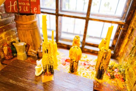 The view of the candle stands in the form of the glass bottle placed on the window-sill