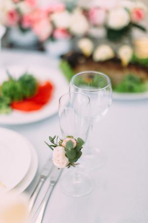 candle: The champagne glass is decorated with little white rose