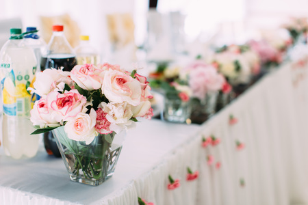candle: Mini-vase with lovely pink and white roses on the wedding table set