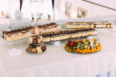 sugarpaste: The wedding table full of different cakes and fruit plate
