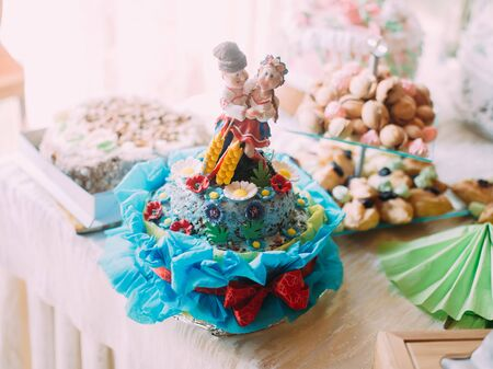 The close-up view of the blue cake decorated with flowers and people dressed in ukrainian clothes Stock Photo