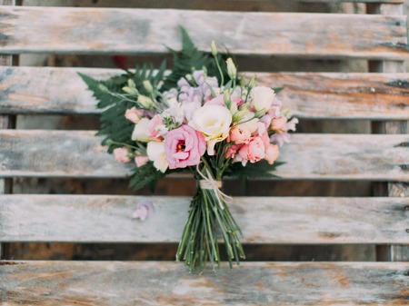 The horizontal portrait of the lovely wedding bouquet of colourful roses placed on the wooden background