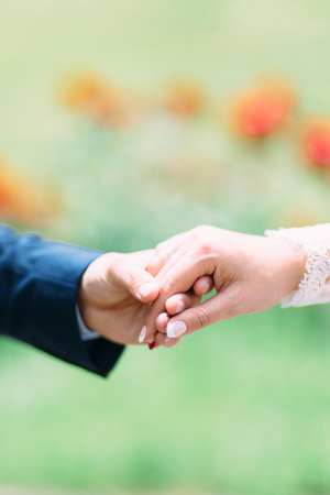 arm bouquet: Theholding hands of the newlywed couple Stock Photo