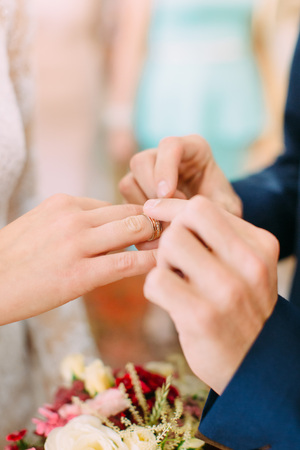 Close-up view of the hands of groom putting the wedding ring on the finger of bride Stock Photo