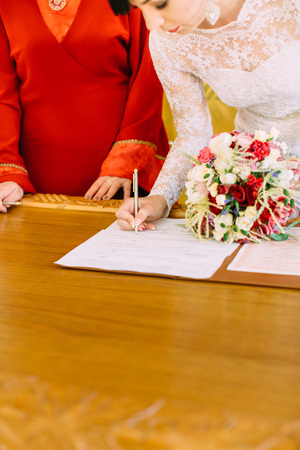 Close-up view of the bride signing the wedding document while holding the bouquet Stock Photo