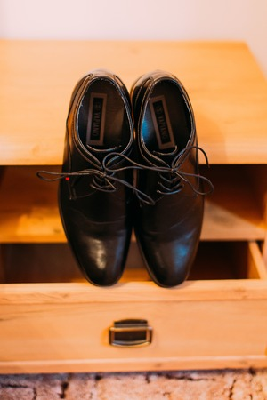 The close-up view of the groom wedding shoes on the wardrobe
