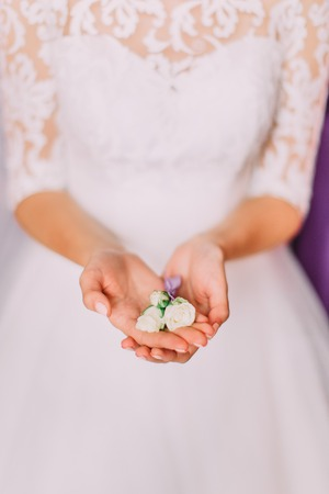 Little white rose boutonniere in the hands of the bride