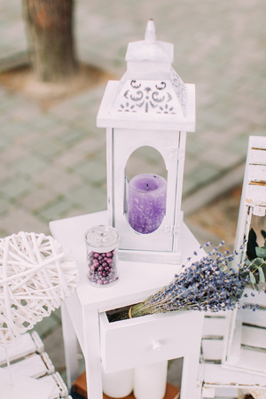 healthfulness: Close-up view of the vintage candle stand laying near the dry lavender bouquet. Wedding concept Stock Photo
