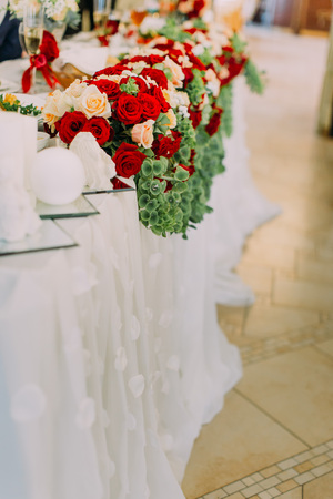 The close-up side view of the red and white roses decorate the wedding table Stock Photo