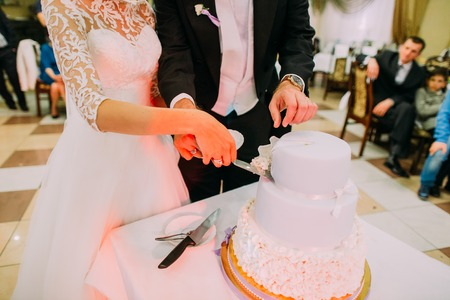 Close-up view of the hands of the newlyweds taking the first piece of the wedding cake out Stock Photo