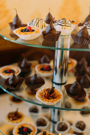 Close-up view of the different cupcakes decorated with fruits and caramel sauce placed on the glass dessert stand