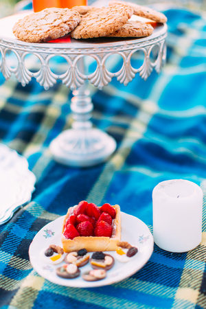 The plate with sponge strawberry cake and chocolade candies are placed between the white small candle and boar with cookies. Stock Photo