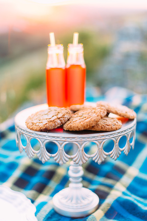 The close-up vertical photo of the white board with cookies and two glass bottles with orange juice in the mountains during the sunset