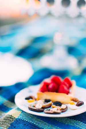 The close-up photo of the delicious sponge strawberry cake and chocolade candies at the blurred background of the blue plaid